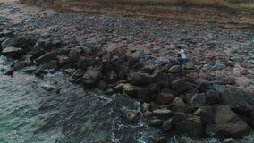 Ideia aérea dos pares que andam em uma praia rochoso filme