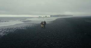 Ideia aérea traseira dos pares novos do moderno que andam na praia vulcânica preta em Islândia O homem e a mulher apreciam o mar filme