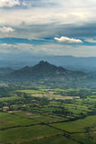 A ideia aérea temperamental, misteriosa do verde cultivou campos na frente das montanhas na ilha de Roatan, Honduras Imagens de Stock