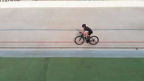 Ideia ascendente próxima da equitação fêmea nova do ciclista no velodrome Treinamento de ciclagem atrativo da menina na trilha de filme