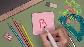 Ideia ascendente próxima da mão da mulher que escreve B mais a marca no bloco de notas pegajoso vídeos de arquivo