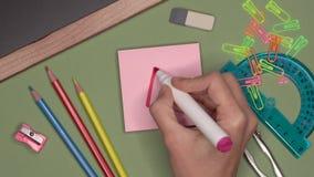 Ideia ascendente próxima da mão da mulher que escreve uma marca excelente positiva no bloco de notas pegajoso video estoque