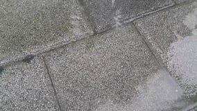 Ideia ascendente próxima das gotas da água chovendo que fazem a ondinha na superfície cinzenta dos tijolos com linhas de cor cinz filme