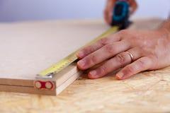 Ideia ascendente próxima das mãos de um homem que medem uma parte de madeira com uma fita handyman medida imagens de stock royalty free