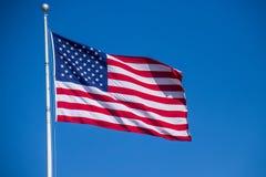 Ideia ascendente próxima do voo da bandeira americana contra um céu azul claro fotografia de stock
