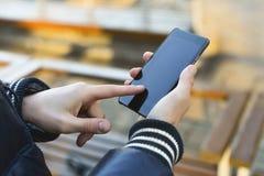 Ideia ascendente pr?xima de sms de datilografia do homem no telefone esperto na rua imagens de stock