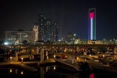Ideia bonita da paisagem famosa da cidade de Abu Dhabi que indica a bandeira dos UAE, as torres de Etihad e os barcos do porto na imagem de stock royalty free