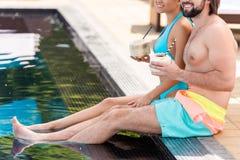 ideia colhida dos pares que relaxam perto da piscina fotos de stock
