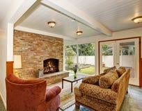 Ideia da área da sala de visitas com parede de tijolo e chaminé, teto de madeira branco Foto de Stock Royalty Free