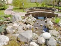 Ideia da corrediça chamada projeto de Alpino da paisagem Watterfall decorativo, rochas coloridas e plantas verdes Pouca ponte Fotos de Stock Royalty Free