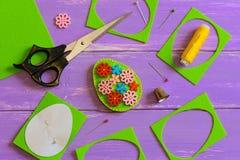 Ideia da decoração do ovo da páscoa de feltro O ovo da páscoa feito a mão de feltro com a flor de madeira colorida abotoa-se Suca imagem de stock