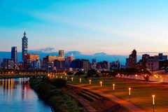 Ideia da noite da cidade de Taipei pelo beira-rio com arranha-céus e de reflexões bonitas na água lisa Imagens de Stock