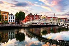 Ideia da noite de Ha iluminado famoso Penny Bridge em Dublin, Irlanda no por do sol foto de stock