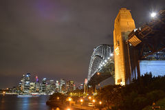 Ideia da noite de Sydney Harbour Bridge & da skyline circular do cais Fotografia de Stock Royalty Free