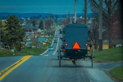 Ideia da parte traseira de um antiquado, carrinho de Amish com uma equitação na estrada rural do cascalho imagem de stock royalty free