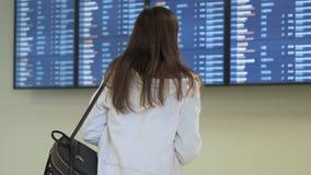 Ideia da parte traseira da programação de voo fêmea da verificação do viajante na placa da partida no aeroporto vídeos de arquivo