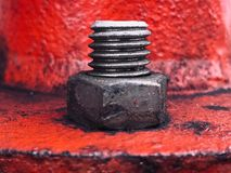 Ideia da porca e do parafuso de aço no aço vermelho fotos de stock royalty free