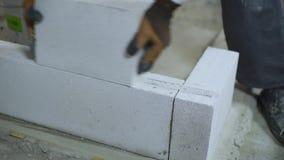 Ideia das mãos do construtor que esfregam o bloco para personalizá-lo para abaixar a camada video estoque