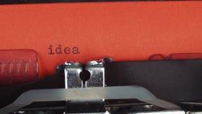 Ideia - datilografada em uma máquina de escrever velha do vintage Impresso no papel vermelho O papel vermelho é introduzido na má filme