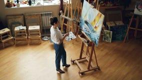 Ideia de ângulo alto do seascape brilhante da pintura ocupada da jovem senhora que trabalha apenas no estúdio usando a paleta e a filme