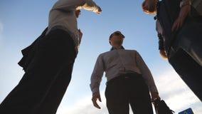 Ideia de baixo ângulo de três homens de negócio que estão exteriores e da fala Os homens de negócios encontram-se e falando fora  vídeos de arquivo