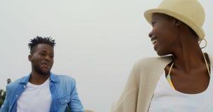 Ideia de baixo ?ngulo dos pares afro-americanos que andam com em conjunto sobre a praia 4k filme