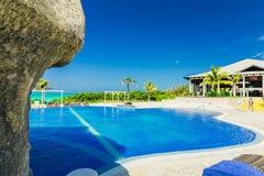 ideia de convite da piscina e de terras douradas do hotel da tulipa com os povos que relaxam no fundo Fotos de Stock