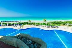 ideia de convite da piscina e de terras douradas do hotel da tulipa com os povos que relaxam no fundo Fotografia de Stock