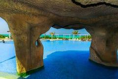 Ideia de convite lindo da gruta e de terras douradas da piscina do hotel da tulipa com os povos que relaxam no fundo Imagem de Stock Royalty Free