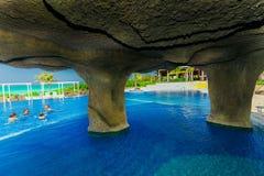 Ideia de convite lindo da piscina e de terras douradas do hotel da tulipa com os povos que relaxam no fundo Foto de Stock Royalty Free