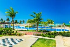 ideia de convite lindo da piscina e de terras douradas do hotel da tulipa com os povos que relaxam no fundo no dia ensolarado Fotografia de Stock Royalty Free