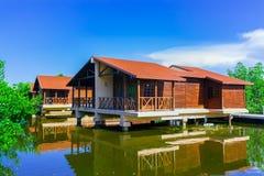 A ideia de convite de surpresa de terras do hotel com casa de campo abriga a posição na água do mar natural no jardim tropical Foto de Stock
