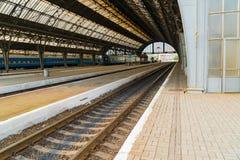 Ideia de perspectiva de uma plataforma na estação de trem central de Lvov com o molde da luz solar nos trens que estacionam pela  Imagens de Stock