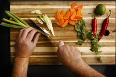 Ideia de plano das mãos que desbastam uma variedade de vegetais fotos de stock royalty free