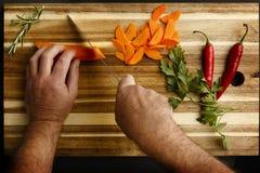 Ideia de plano das mãos que preparam vegetais, em uma placa de desbastamento imagens de stock royalty free
