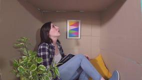 Ideia de pouca sala, jovem mulher desapontada do conceito em uma caixa de cartão pequena com um portátil filme
