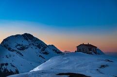 Ideia de um abrigo nas montanhas cobertos de neve de Vardousia em Grécia no por do sol Imagem de Stock