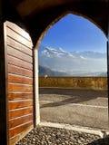 Ideia de uma paisagem surpreendente através de uma porta antiga imagem de stock