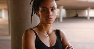 Ideia dianteira da música de escuta da mulher afro-americano nova em fones de ouvido na cidade 4k video estoque