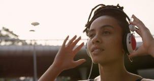 Ideia dianteira da música de escuta da mulher afro-americano nova em fones de ouvido na cidade 4k vídeos de arquivo