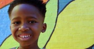 Ideia dianteira da posição afro-americano feliz da estudante contra a parede na escola 4k filme