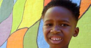 Ideia dianteira da posição afro-americano feliz da estudante contra a parede na escola 4k vídeos de arquivo
