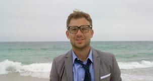 Ideia dianteira da posição caucasiano do homem de negócios na praia 4k vídeos de arquivo