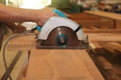A ideia dianteira das mãos do carpinteiro superior que cortam uma parte de madeira contra a circular elétrica considerou no woods fotografia de stock