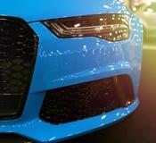 Ideia dianteira do esporte luxuoso moderno azul com luz alaranjada macia do sol Detalhes do exterior do carro Farol de um carro d imagem de stock