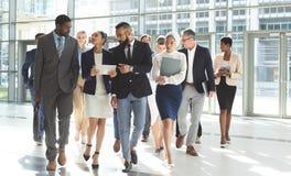 Ideia dianteira do grupo de executivos diversos que andam junto no escritório da entrada fotos de stock royalty free