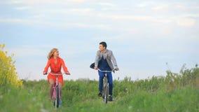 Ideia dianteira do uple alegre bonito do co dos amantes que montam ativamente as bicicletas ao longo do campo de florescência ver video estoque