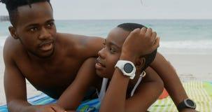 Ideia dianteira dos pares afro-americanos que relaxam na praia 4k video estoque