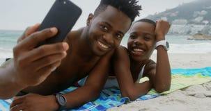 Ideia dianteira dos pares afro-americanos que tomam o selfie com telefone celular na praia 4k filme