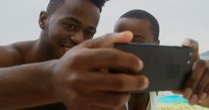 Ideia dianteira dos pares afro-americanos que tomam o selfie com telefone celular na praia 4k vídeos de arquivo